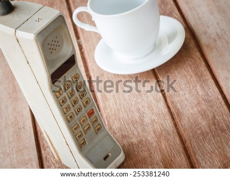 vintage mobile phone with cup of coffee - stock photo