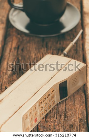 vintage mobile phone with cup of coffee (vintage style) - stock photo