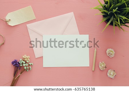 vintage mockup with flowers and blank letter on pink wooden background