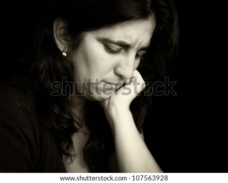Vintage monochromatic portrait of a sad and depressed hispanic woman with a thoughtful expression isolated on black