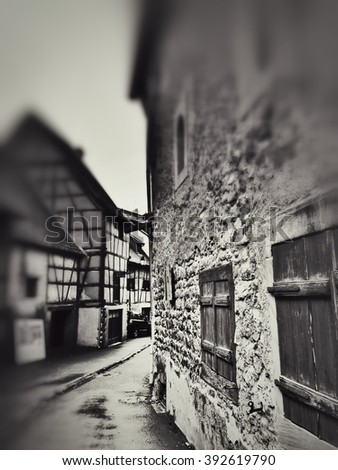 vintage monochrome focused street view of a traditional franchement village in Alsace - stock photo
