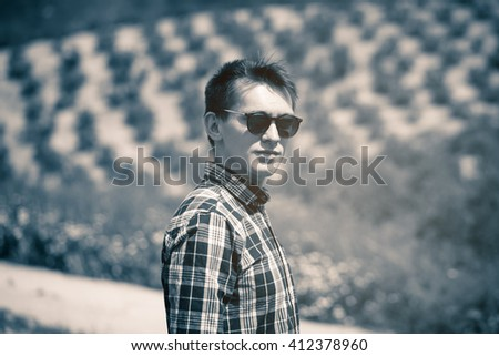 Vintage monochrome portrait of young man in sunglasses at the countryside in Andalusia, Spain. - stock photo