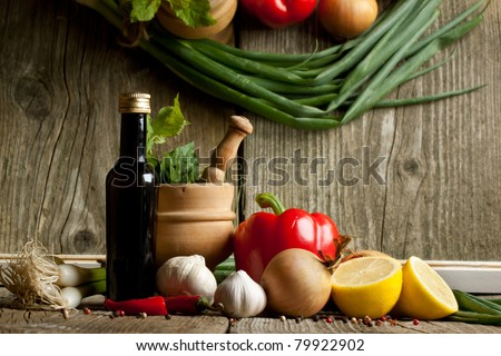 Vintage mortar and vegetables paprika, pepper and garlic on old wooden table with reflex in mirror - stock photo
