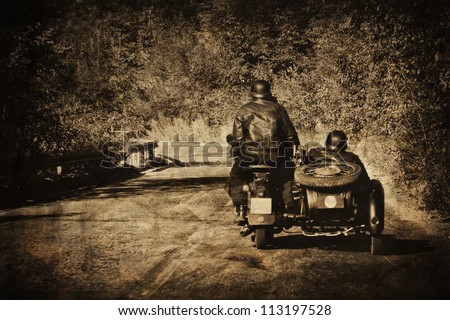 vintage moto biker in the road - stock photo