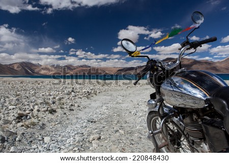 Vintage motorcycle on background of beautiful mountain lake. Pangong lake in Ladakh by vintage motorcycle. Offroad trail leading to highland lake with vintage motorcycle. - stock photo