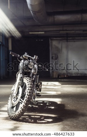 Vintage motorcycle standing in a dark building in the rays of sunlight. Vertical Front view