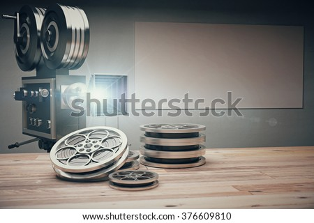 Vintage movie camera with Old style cassettes and film on wooden table - stock photo