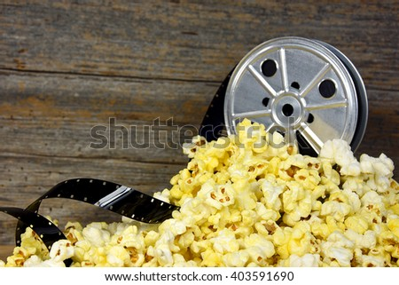 vintage movie reel with pile of popcorn - stock photo
