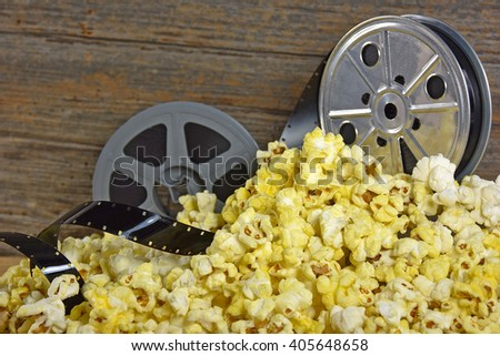 vintage movie reels and film in a pile of popcorn - stock photo