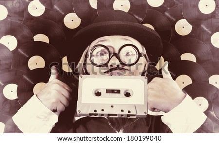 Vintage music concept with a geeky woman giving thumbs up for louder volume while holding retro audio cassette in mouth, on vinyl record background