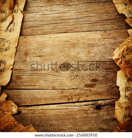 Vintage music sheet on wooden background - stock photo