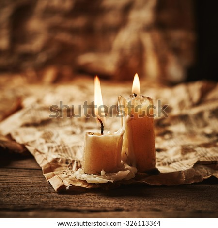 Vintage music sheets with candle on wooden background - stock photo