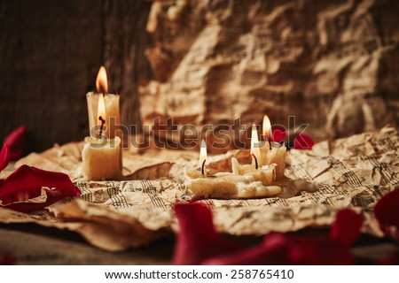 Vintage music sheets with rose petals and candles on wooden background - stock photo