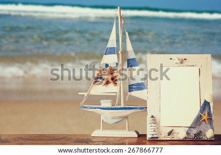 vintage nautical frame with starfish on wooden table and sea beach background. retro filtered image