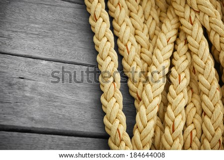 Vintage nautical knots background with copy-space. Big marine sea ropes on wooden desk - stock photo