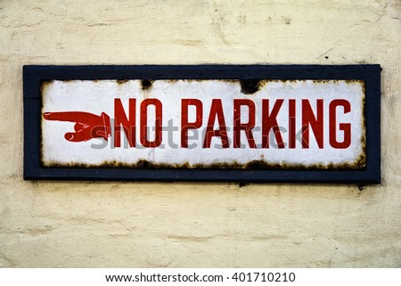 Vintage NO PARKING sign; old enamel sign with Printers fist and red lettering, rusted around edges, mounted on cream brick wall  - stock photo