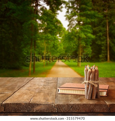 vintage notebook and stack of wooden colorful pencils on wooden texture table in front of countryside forest view - stock photo
