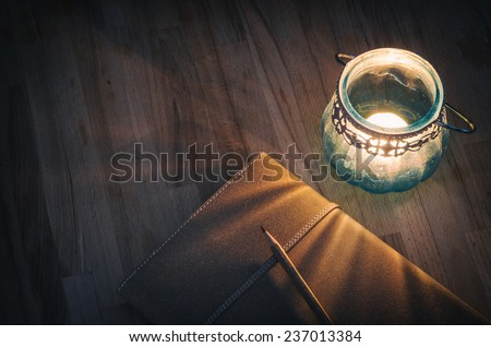 vintage notebook with an old candle on wooden table - stock photo