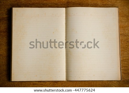 vintage notebook with grunge paper on wood table