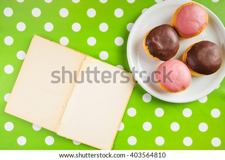 Vintage notebook with recipe for delicious homemade doughnuts with topping, top view over polka dotted surface. - stock photo