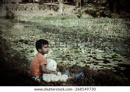 vintage of little boy sitting along with white bear at the swamp  - stock photo
