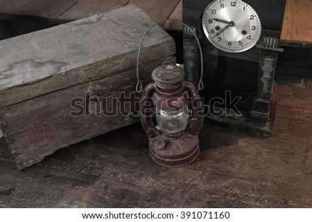 Vintage oil lamp ,old wooden box and alarm clock on old wooden touch-up in still life concept ,processed in dark tone - stock photo