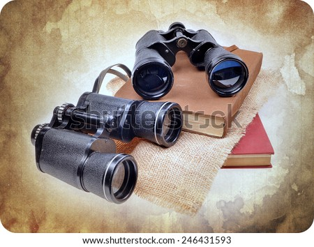 Vintage old  binoculars on ancient book . Nostalgic vintage background