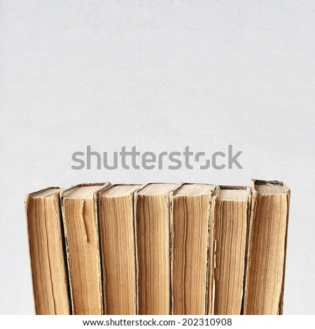 vintage old books near the wall background - stock photo