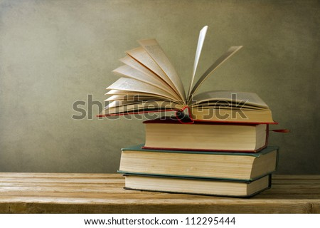 Vintage old books on wooden deck table and grunge background - stock photo