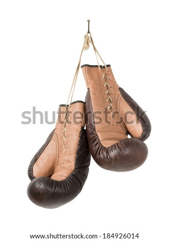 Vintage old boxing gloves hanging with lace on nail isolated over white background. - stock photo