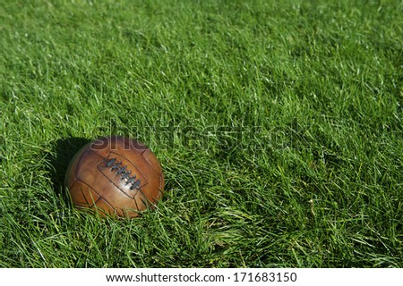 Vintage old brown football old-fashioned soccer ball sits in sunny green grass field  - stock photo