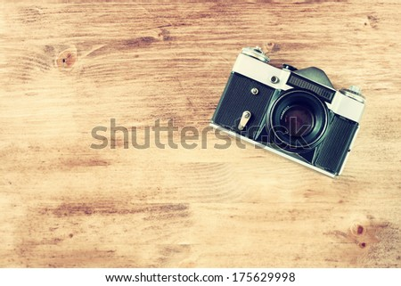 vintage old camera on brown wooden background. room for text. - stock photo