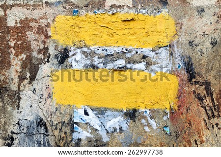 Vintage old damaged wall with cracks, scratches and scraps of paper, painted with yellow paint. Textured background for your concept or project. Great background or texture. - stock photo