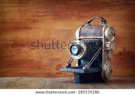 vintage old decorative camera on brown wooden background - stock photo