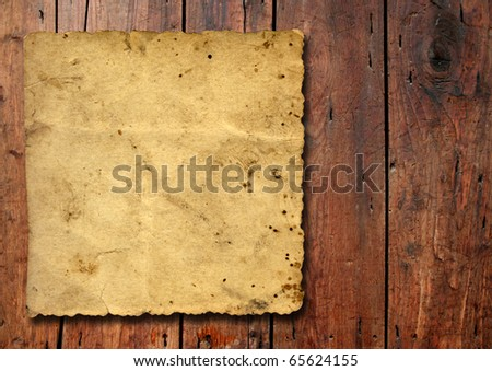 Vintage old grungy paper over ancient wood texture background metaphor for aged, retro, wooden, dirty, textured, manuscript, antique, parchment, book, ancient, weathered or grungy