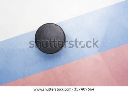 vintage old hockey puck is on the ice with russia flag - stock photo