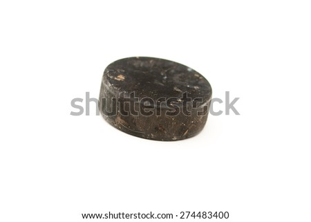 Vintage old hockey puck on white background, used rubber puck, Ice Hockey World Championships, used implements, natural and real photo - stock photo