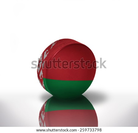 vintage old hockey puck with the belarus flag - stock photo