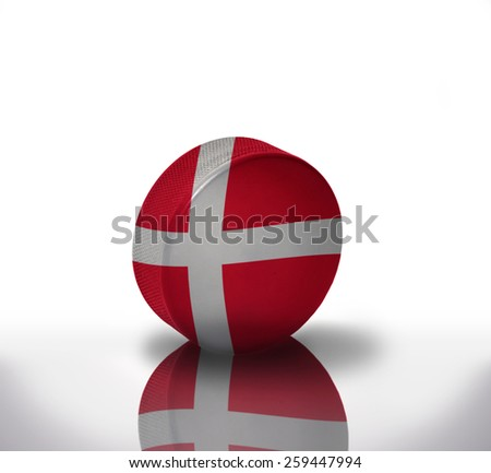 vintage old hockey puck with the danish flag - stock photo