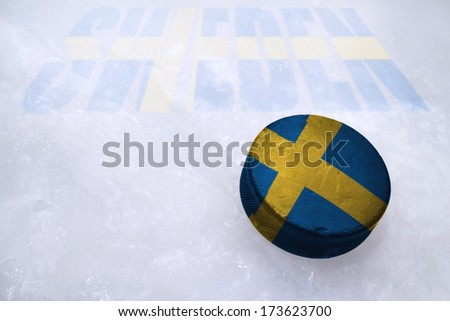 Vintage old hockey puck with the Sweden flag is on the ice - stock photo
