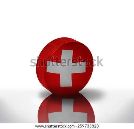 vintage old hockey puck with the swiss flag - stock photo