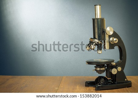 Vintage old microscope on table for science background - stock photo