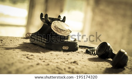 Vintage old phone in ruins. Sepia. Low key. - stock photo