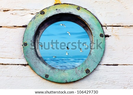Vintage old porthole window with a view of the ocean and birds flying by. - stock photo