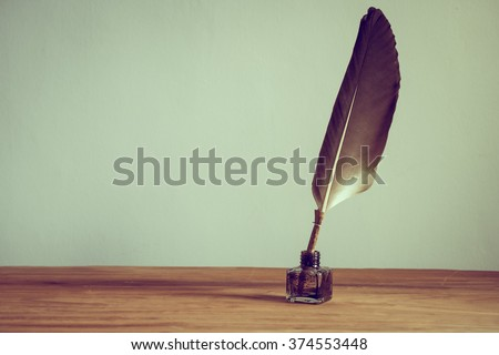 Vintage old quill pen, inkwell on wooden table. Vintage style filtered photo - stock photo