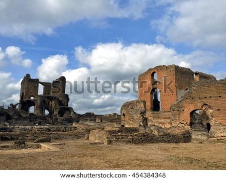 Vintage old Roman empire ruins under blue sky - stock photo