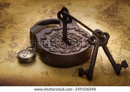 Vintage old rusty padlock with keys and pocketwatch on ancient map, still life - stock photo
