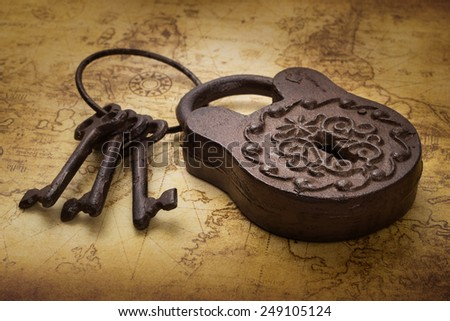 Vintage old rusty padlock with keys on ancient map, still life - stock photo
