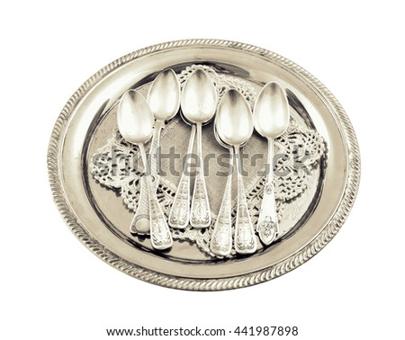 vintage old silverware in a silver tray close-up,isolated white background