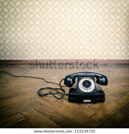 vintage old telephone, black retro phone is on the floor of used parquet  - stock photo
